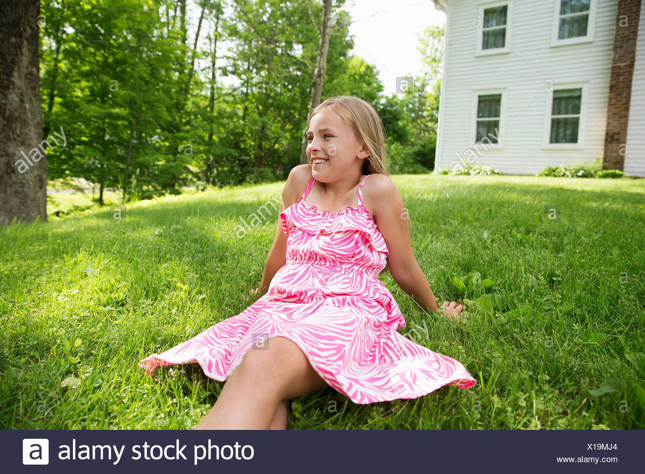 A young girl in a pink patterned sundress sitting on the grass under the trees in a farmhouse garden. - Stock Image