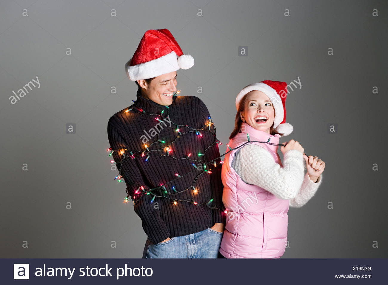 Woman pulling man tied up in christmas lights - Stock Image