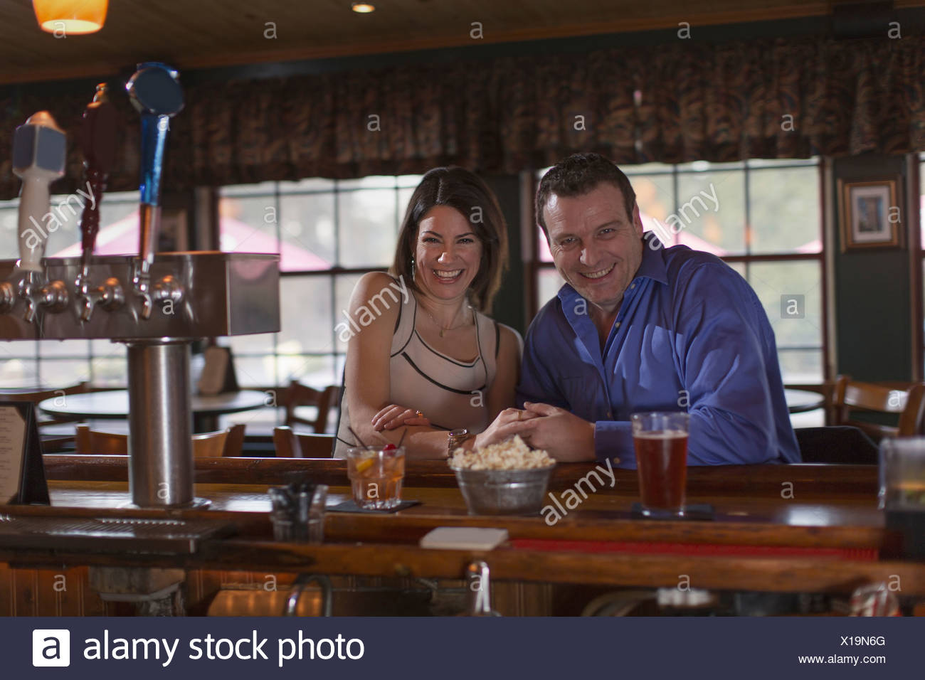 A man and woman side by side seated at a bar smiling On a date  New Hope Pennsylvania USA - Stock Image