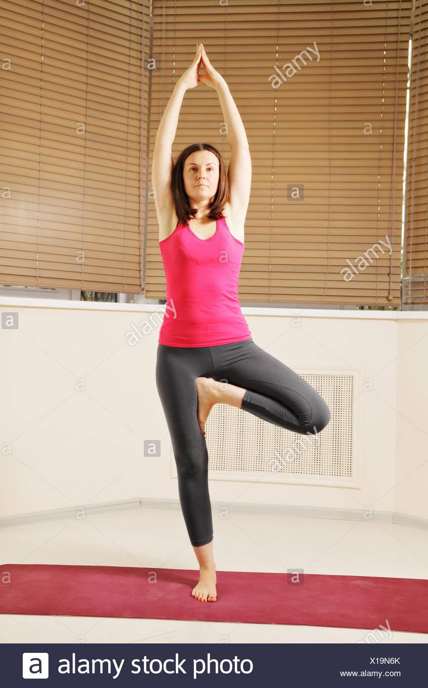 Brunette balancing on one leg yoga pose Stock Photo   Alamy