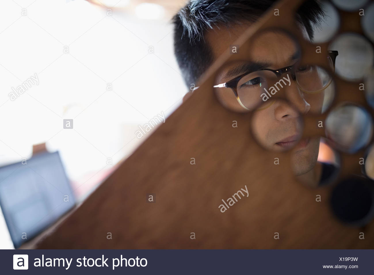Close up serious, focused male engineer examining laser cut wood holes - Stock Image