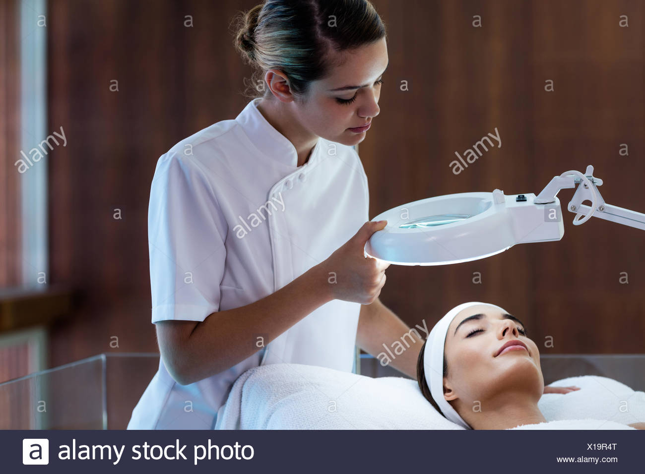 Masseuse looking at woman face Stock Photo