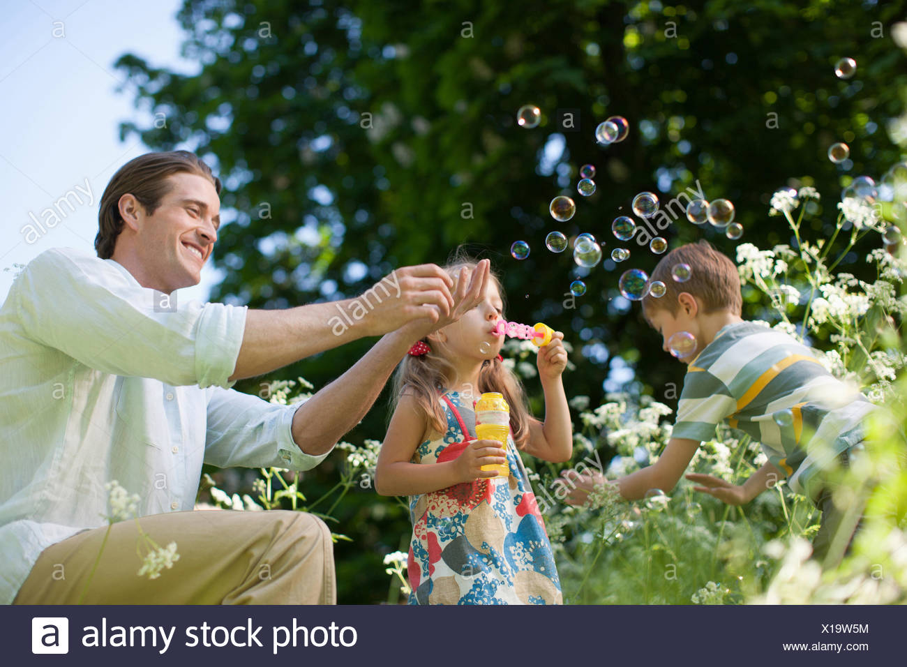 Family playing with bubbles outdoors - Stock Image