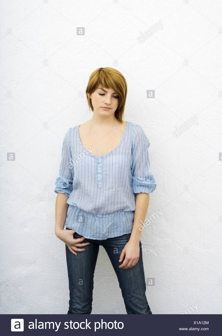 Young woman standing, looking down, portrait, three quarter length - Stock Image