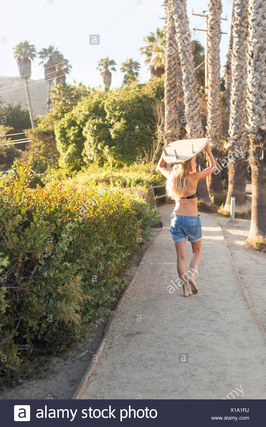 Blond woman in a black bikini and denim shorts carrying a surfboard on a path lined with palm trees. - Stock Image