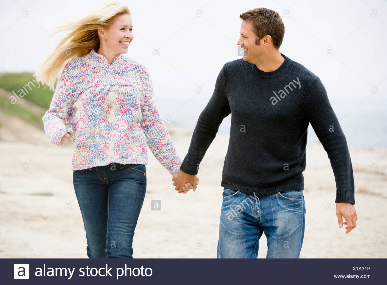 Couple walking at beach holding hands smiling Stock Photo