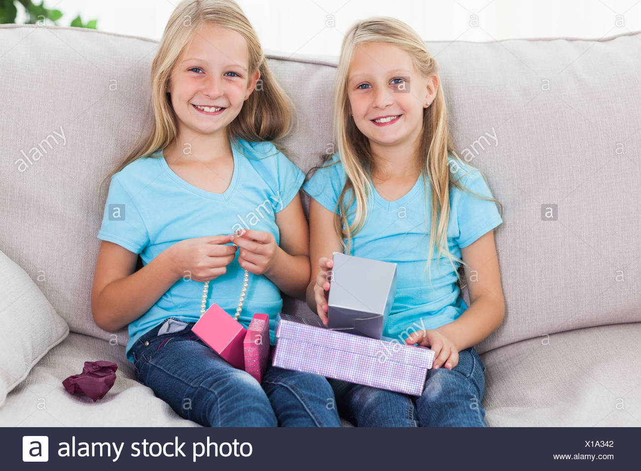 Cute Twins Unwrapping Birthday Gift Sitting On A Couch