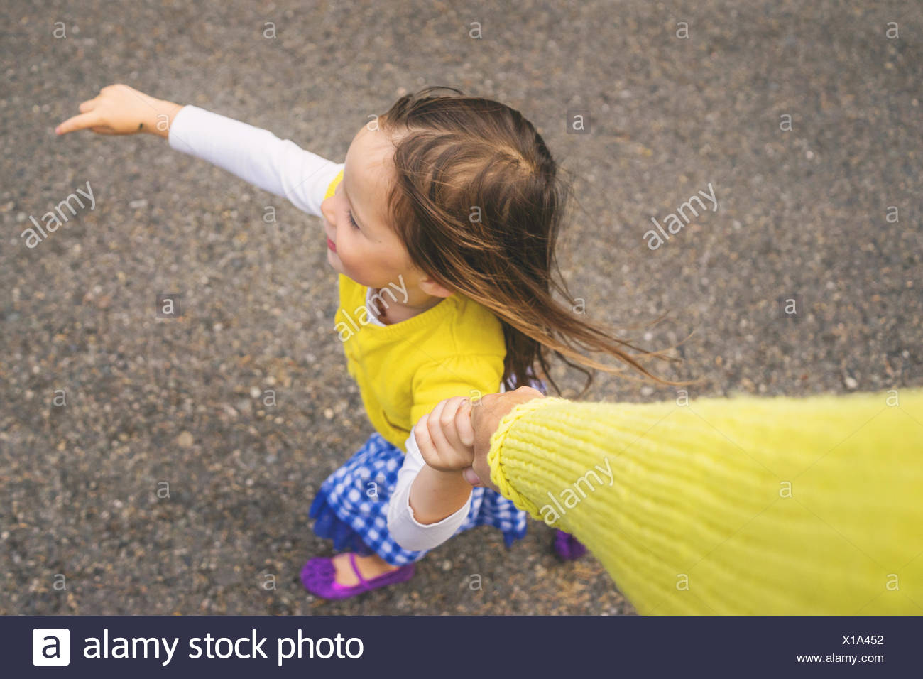 Overhead view of a girl holding her mother's hand Stock Photo