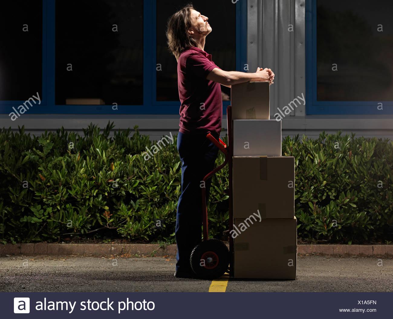 man moving boxes at night - Stock Image