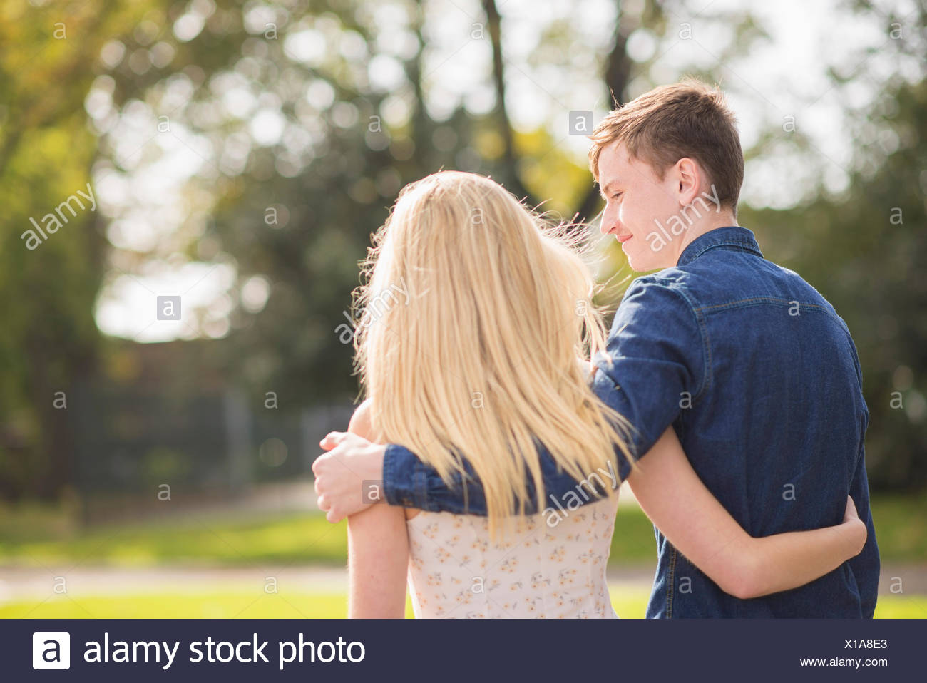 Rear view of romantic young couple strolling in park Stock Photo