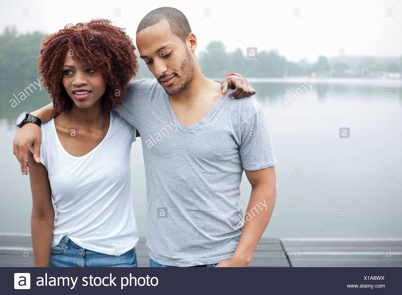 Portrait of young couple by lake with arms around each other - Stock Image
