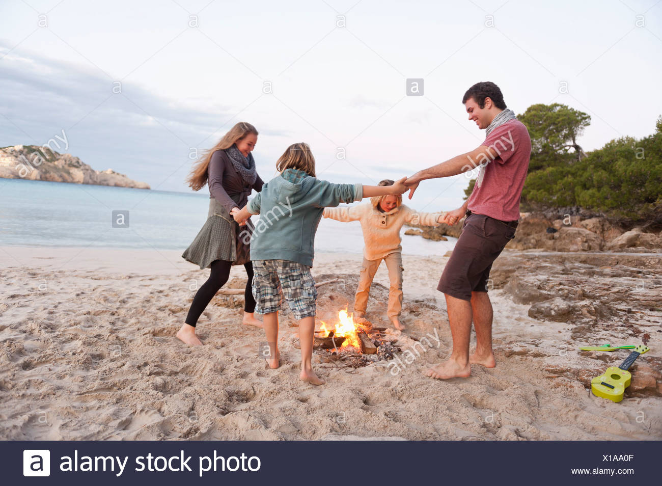 Spain, Mallorca, Friends dancing at camp fire on beach - Stock Image