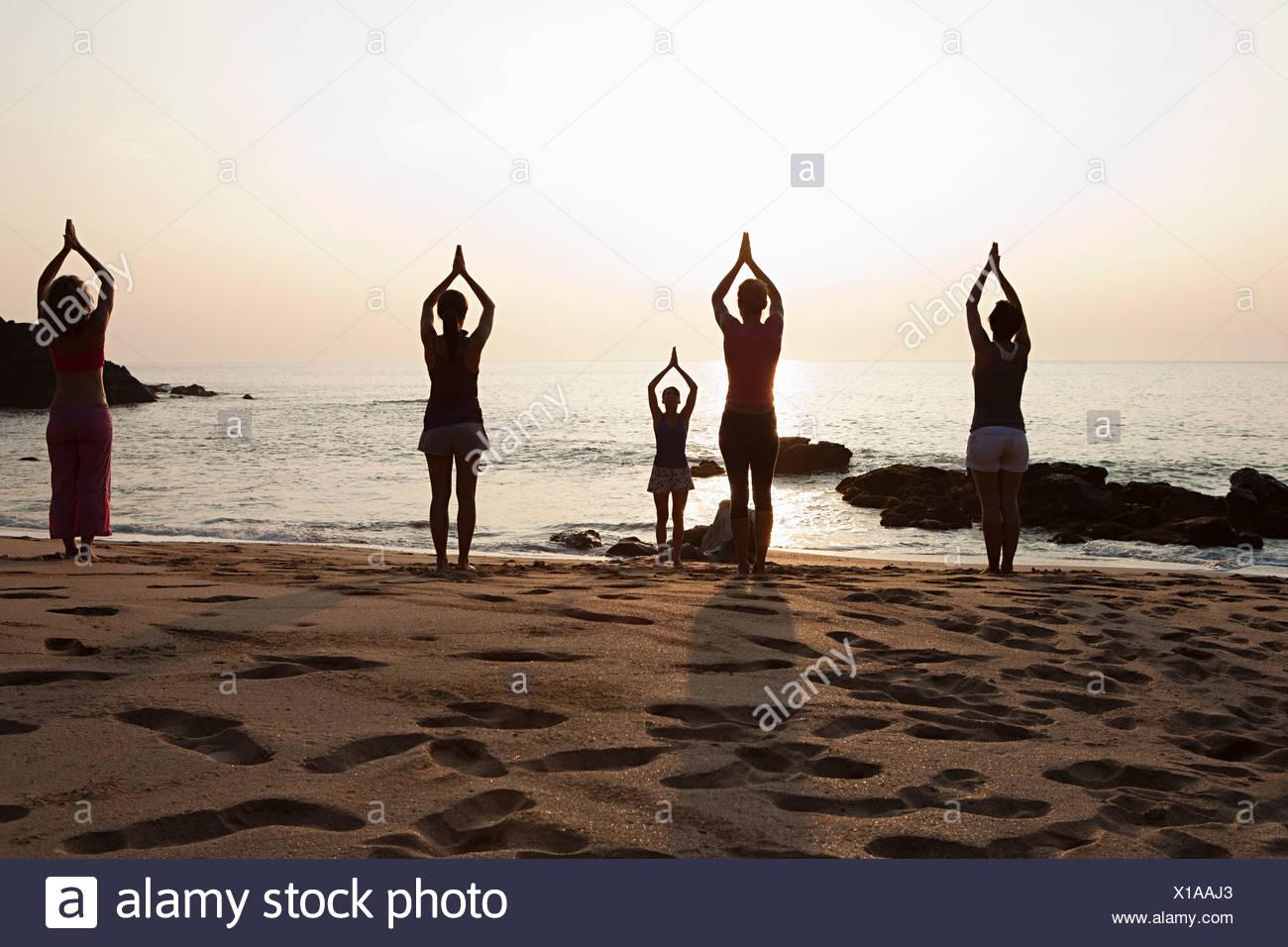 Women practicing yoga on beach at sunset - Stock Image