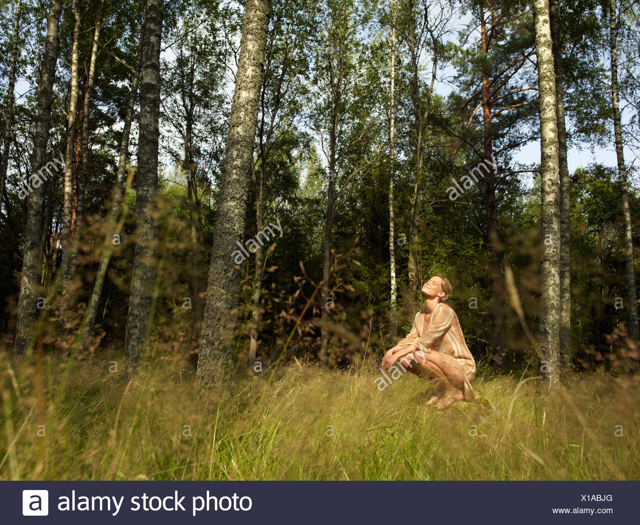 Woman crouching on a large rock in forest smiling. - Stock Image