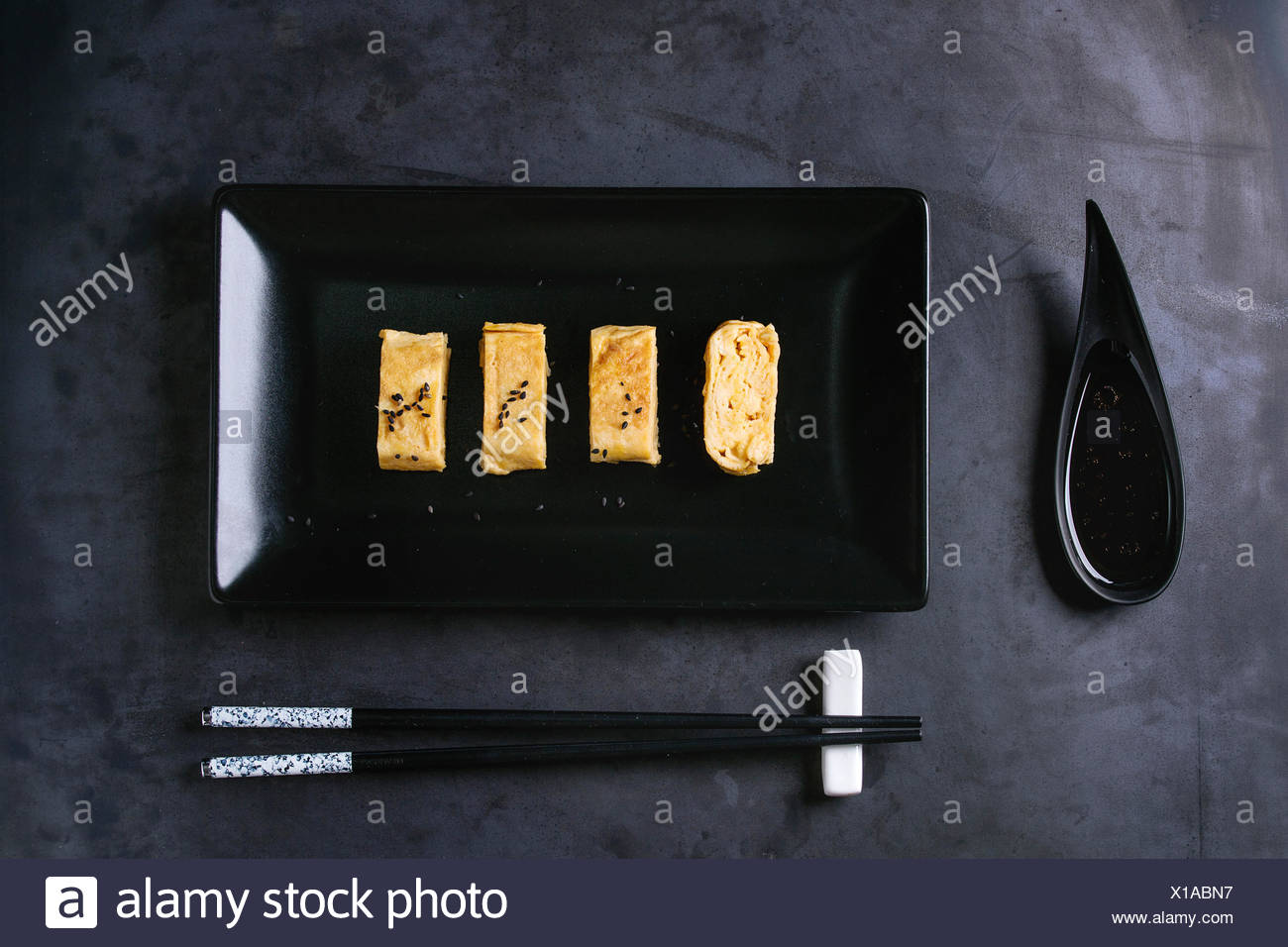 Japanese Rolled Omelette Tamagoyaki sliced with black seasame seeds and soy sauce, served in black square ceramic plate with chopsticks over dark meta - Stock Image