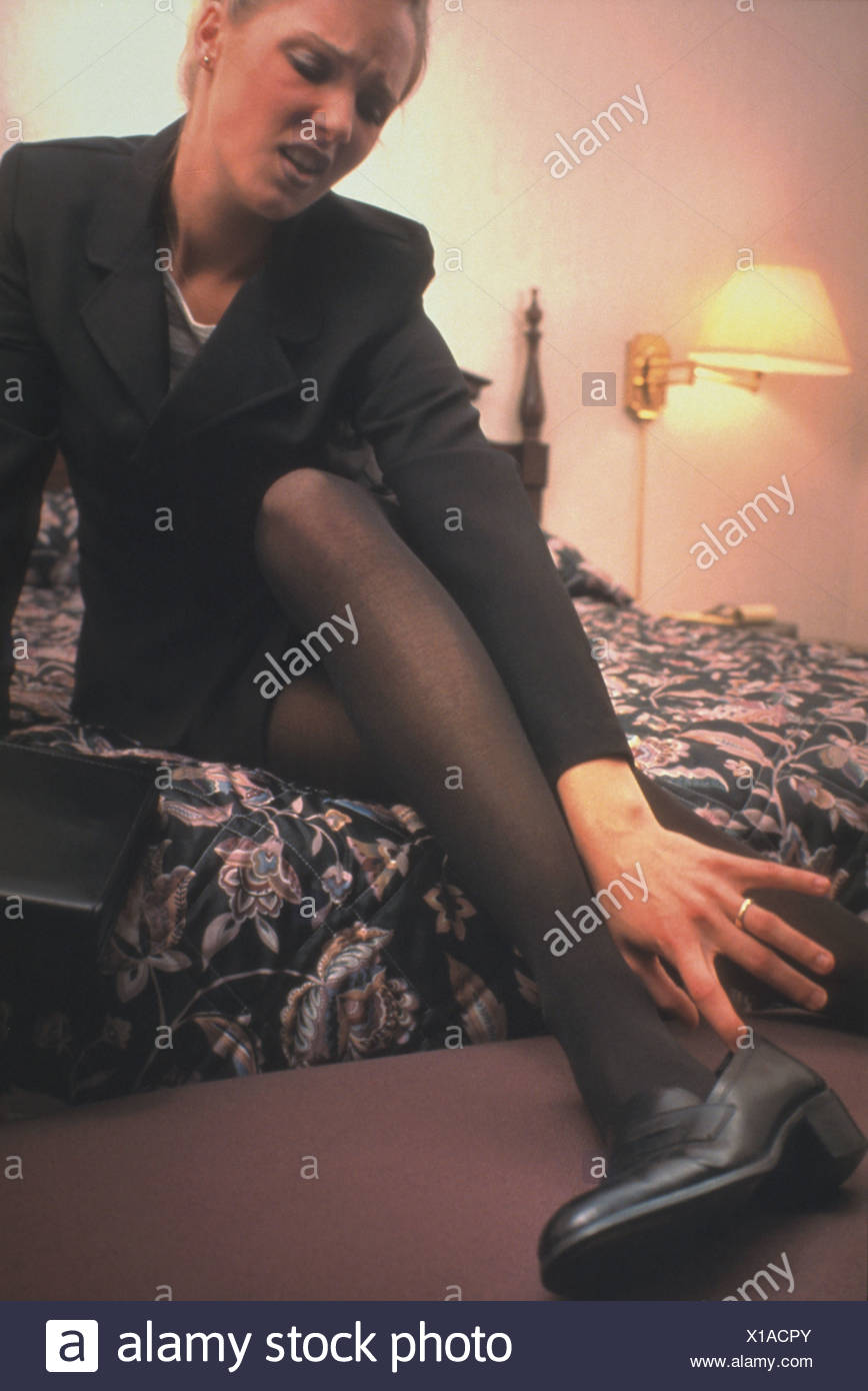A tired businesswoman sits on her bed and kicks her shoes off to relax her aching feet - Stock Image
