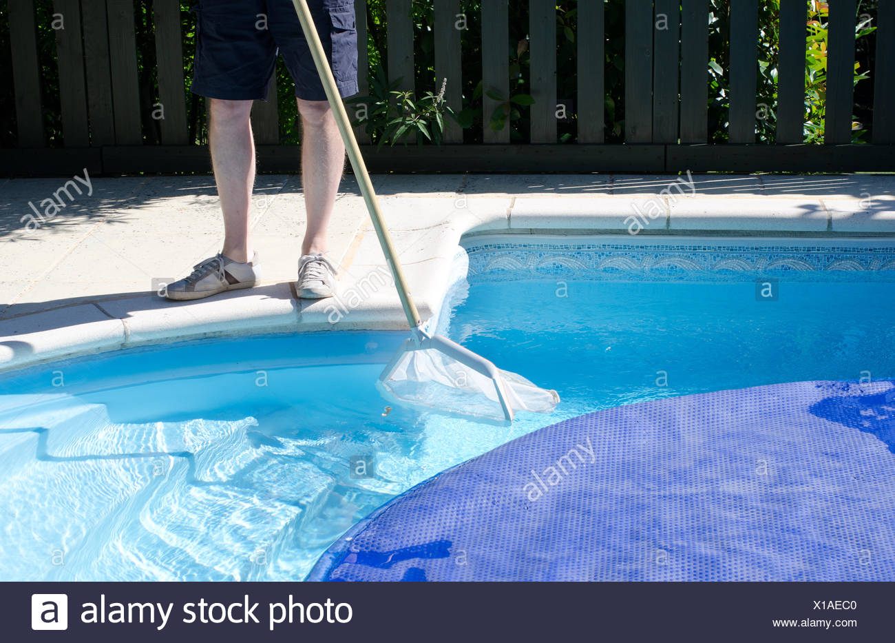 A man with a net cleaning the last part of the swimming pool ...