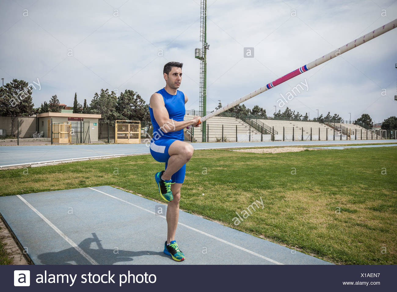 Young male pole vaulter pole vaulting at sport facility - Stock Image