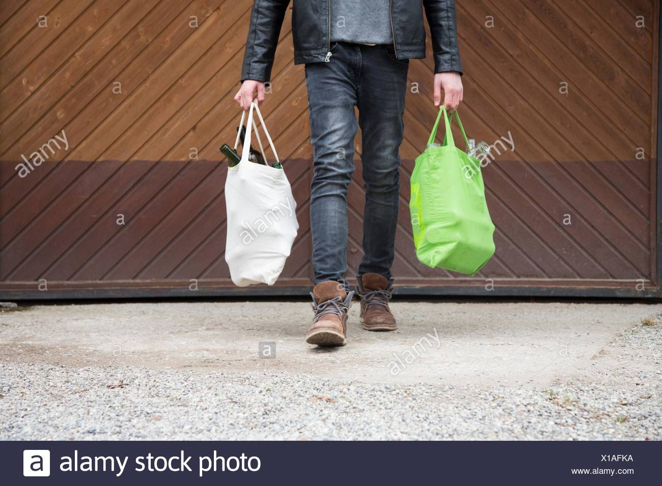 Teenage boy carrying reusable shopping bags full of empty bottles for recycling - Stock Image