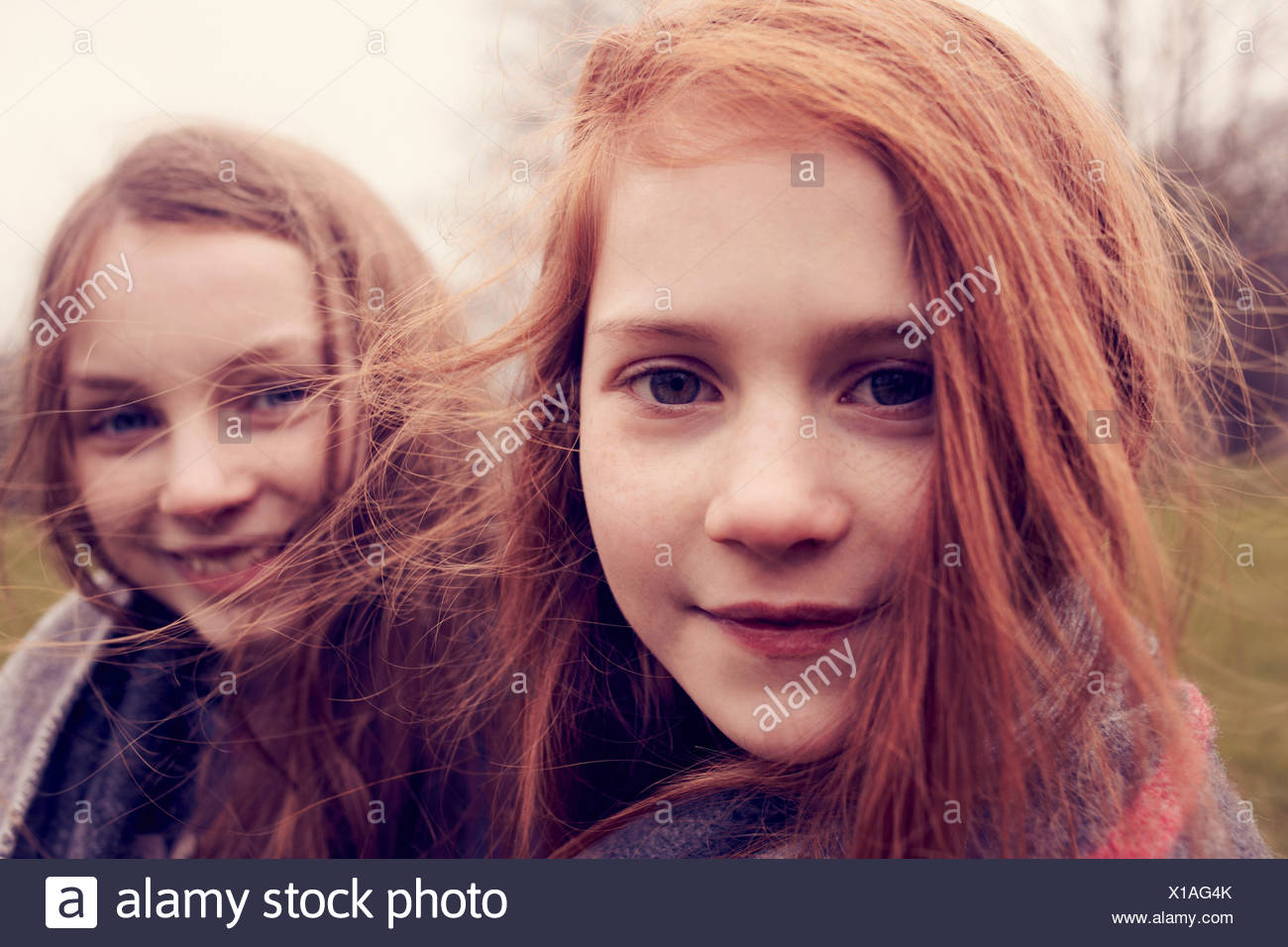 Portrait of girls wrapped in a blanket outdoors, smiling - Stock Image
