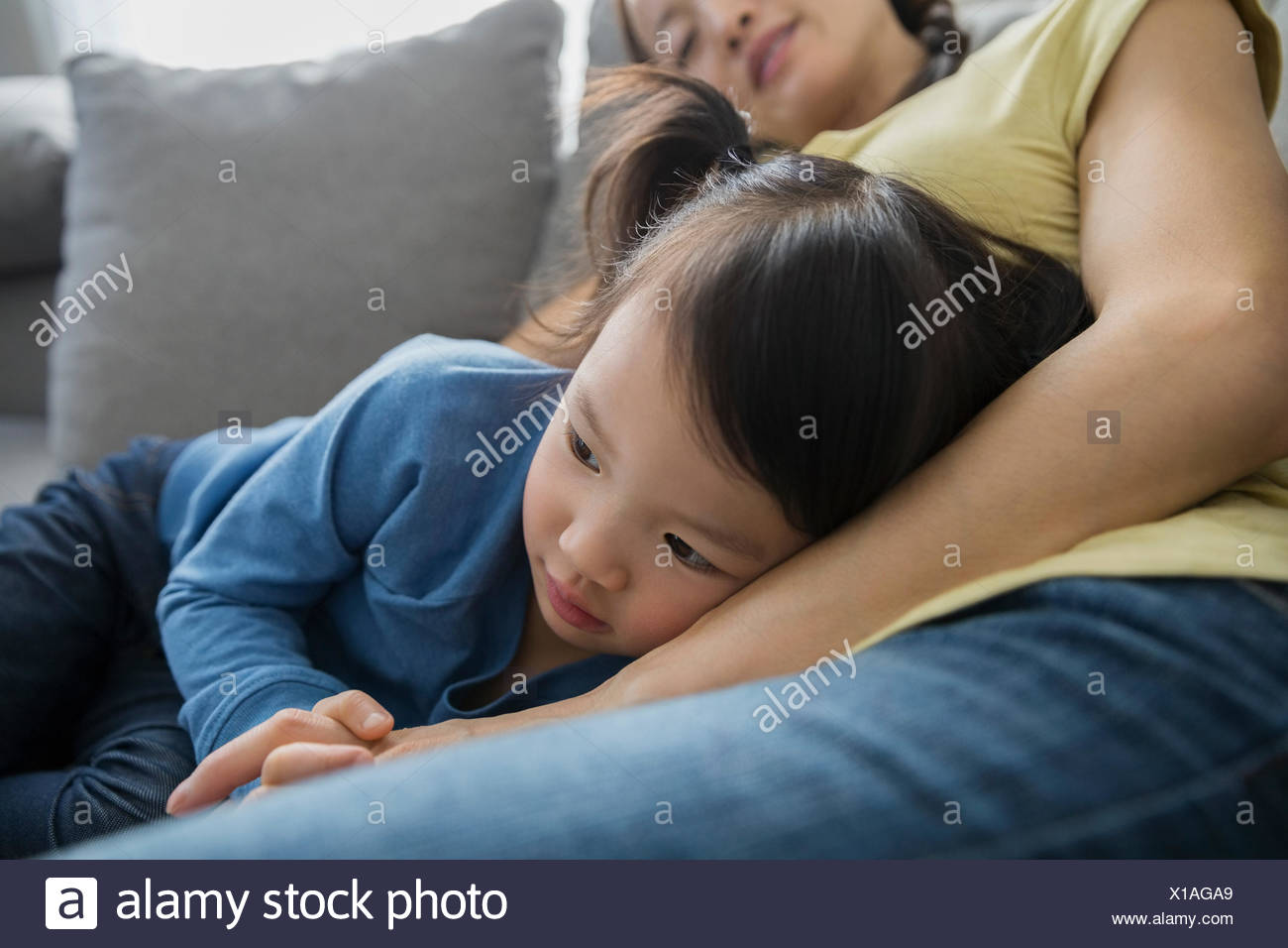 Close up of tired mother and daughter cuddling - Stock Image