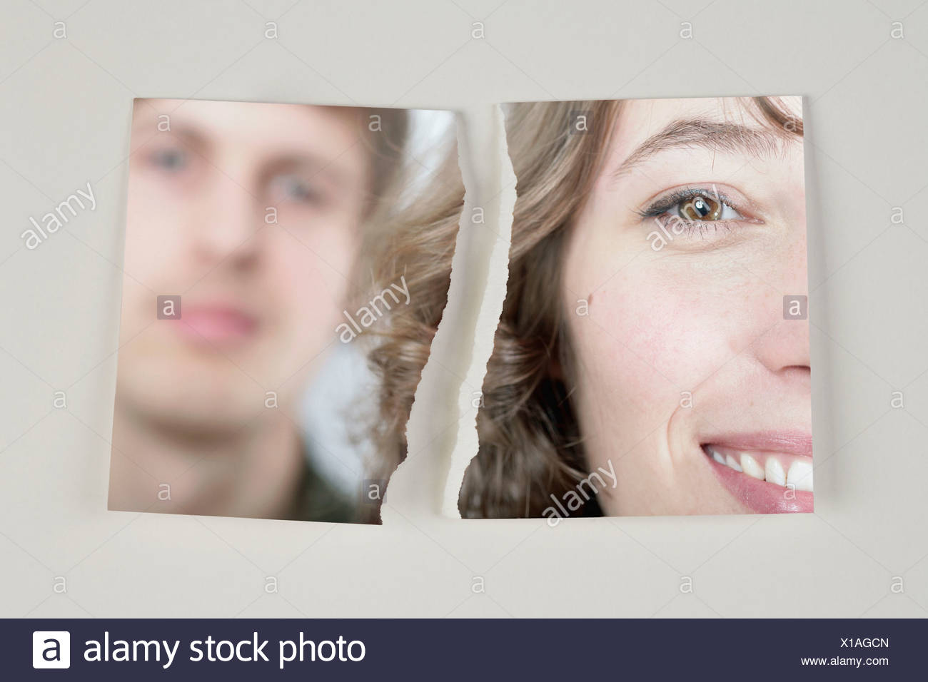 A photograph of a heterosexual couple torn in half - Stock Image