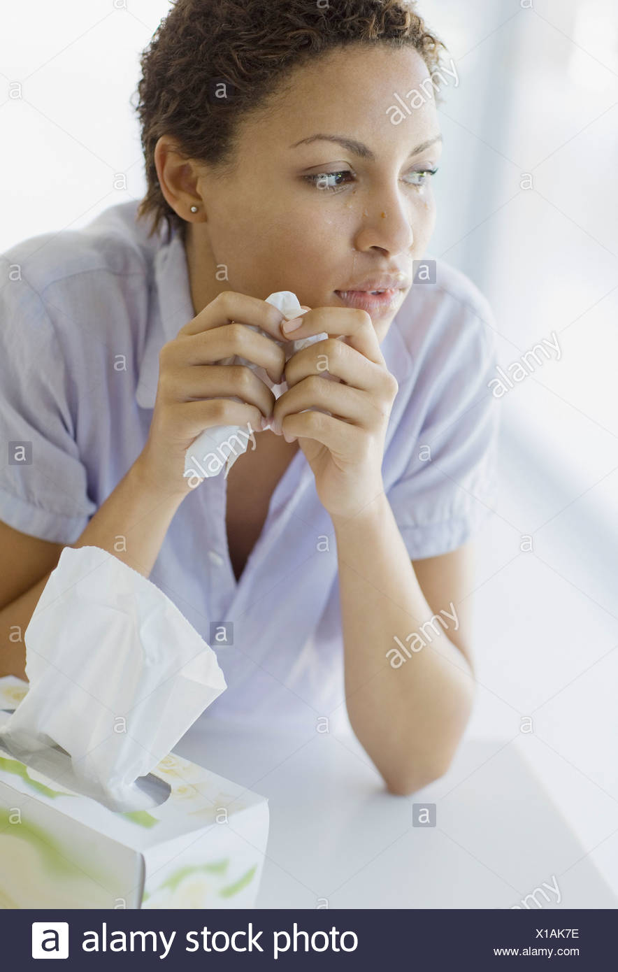 Crying woman holding tissue - Stock Image