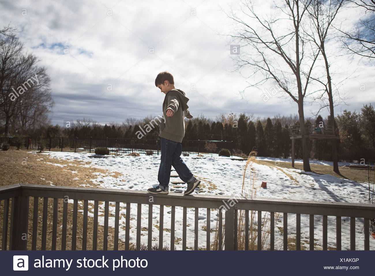 Boy walking along top of fence in park Stock Photo