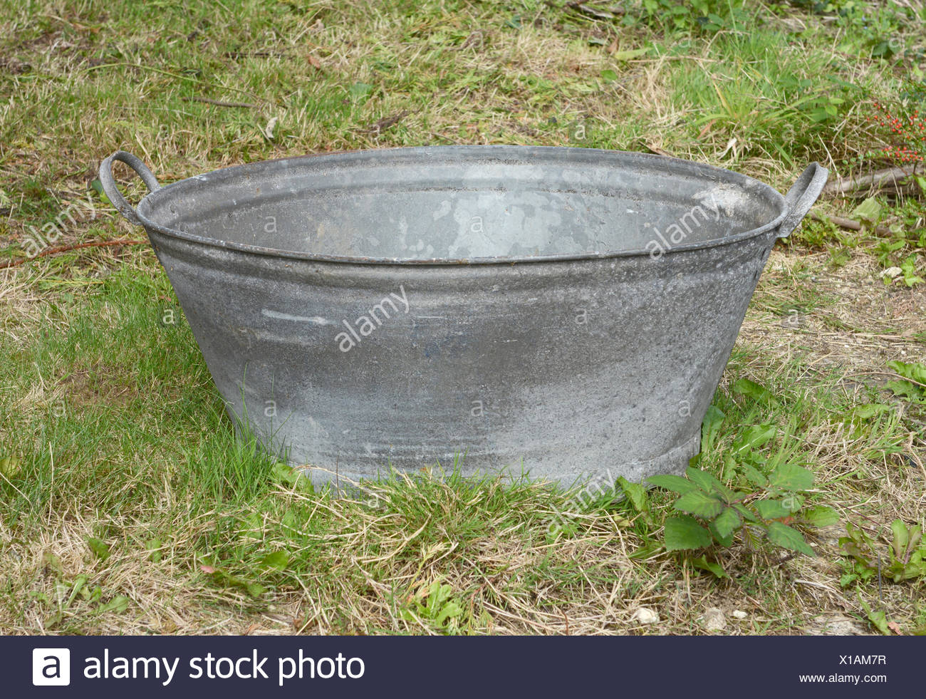 Empty Tin Bath Standing On Rough Grass And Weeds   Stock Image