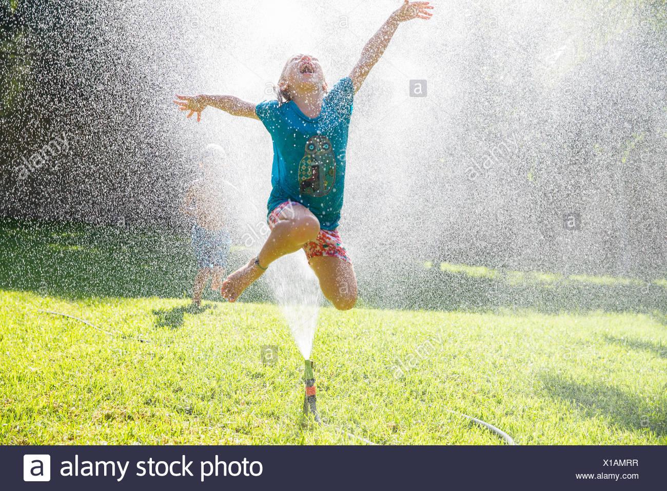 Girl jumping over water sprinkler in garden - Stock Image