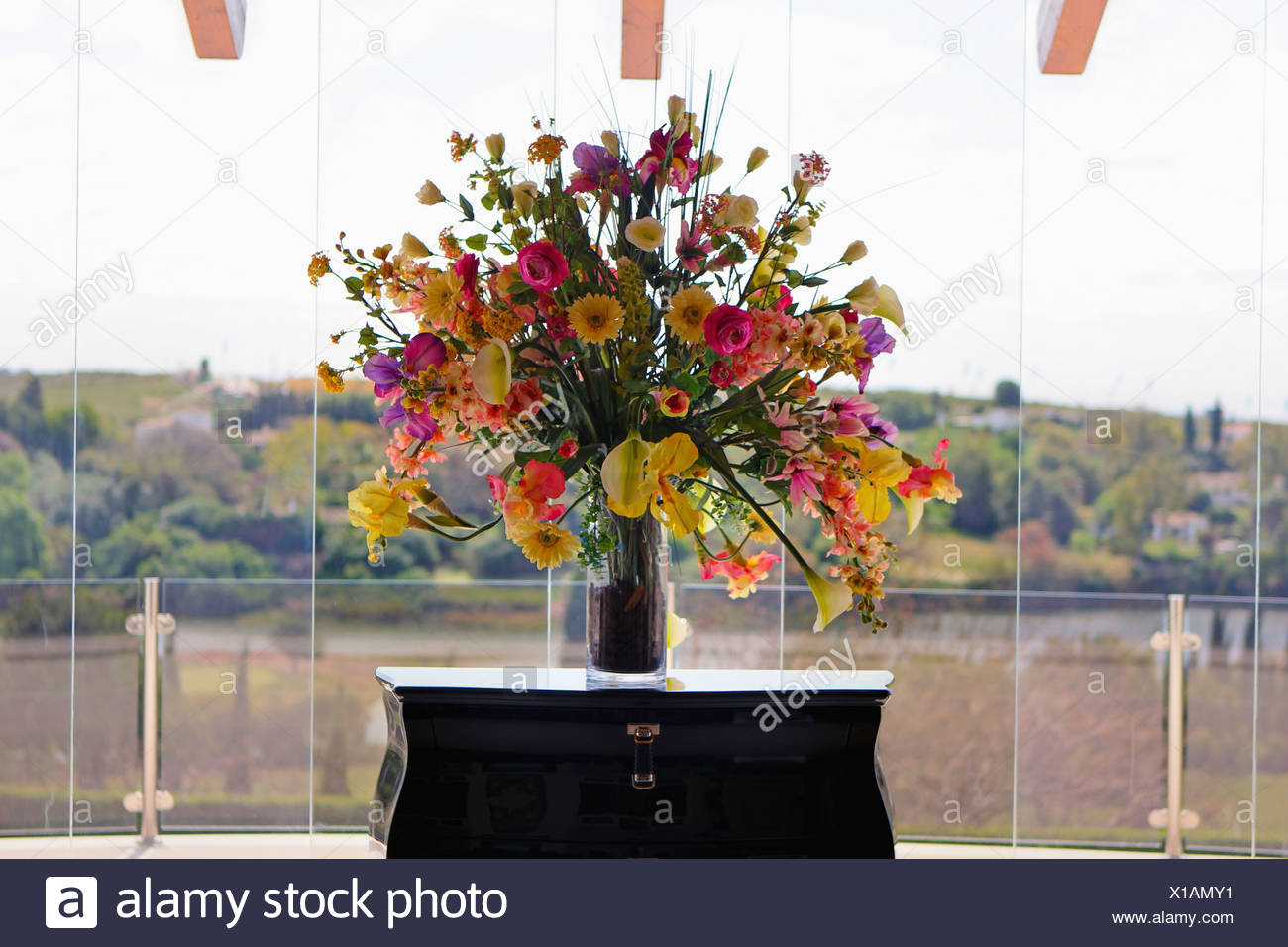 Formal Floral Arrangement Of Pink And Yellow Summer Flowers In Vase On Table Beside Large Windows In Modern Hall Stock Photo Alamy