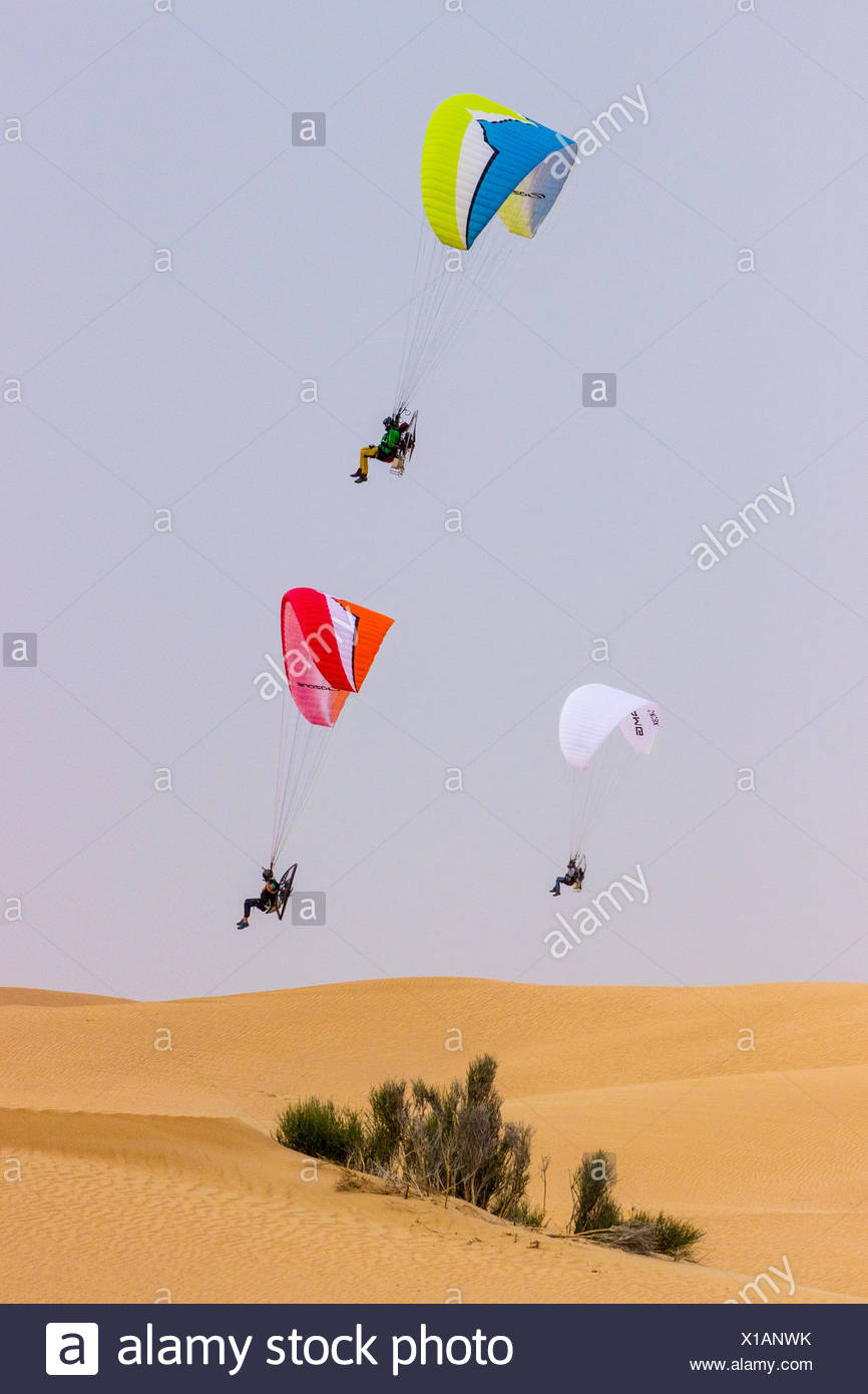 Paramotor pilots flying low over the sand dunes of the Arabian desert. - Stock Image