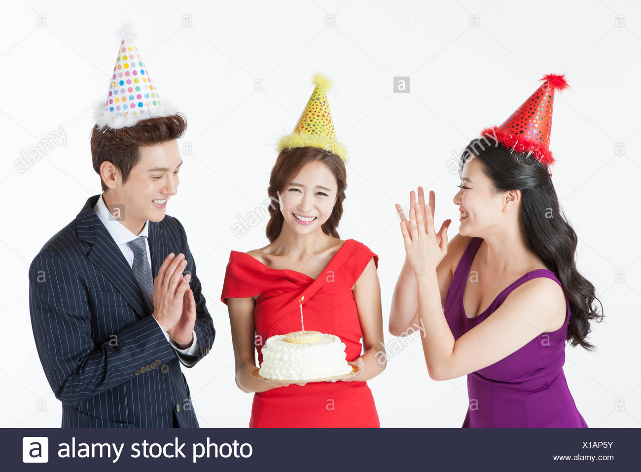Three Young Adults Celebrating The Womans Birthday With A Cake All In Party Hat
