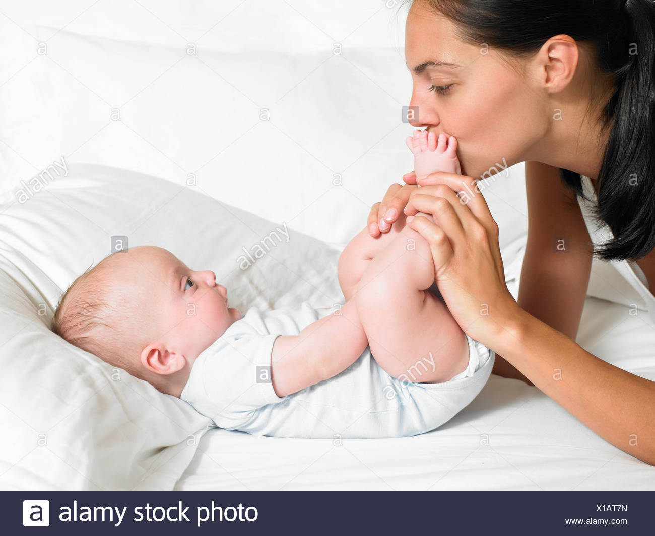 Mother kissing her new-born baby's feet Stock Photo