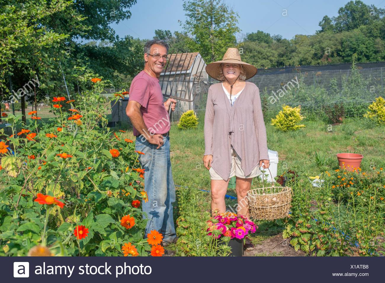 Portrait of male and female farmers in garden - Stock Image