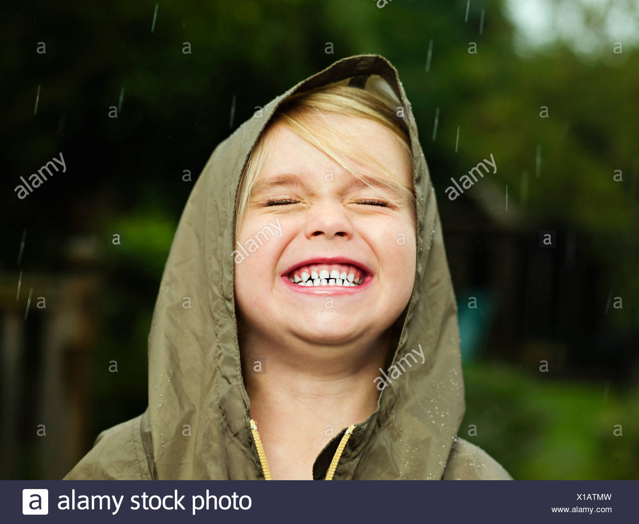 Girl smiling while it rains - Stock Image