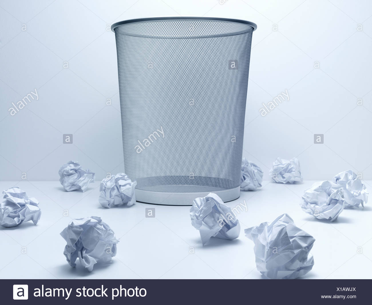 Crumpled balls of paper beside wastebasket - Stock Image