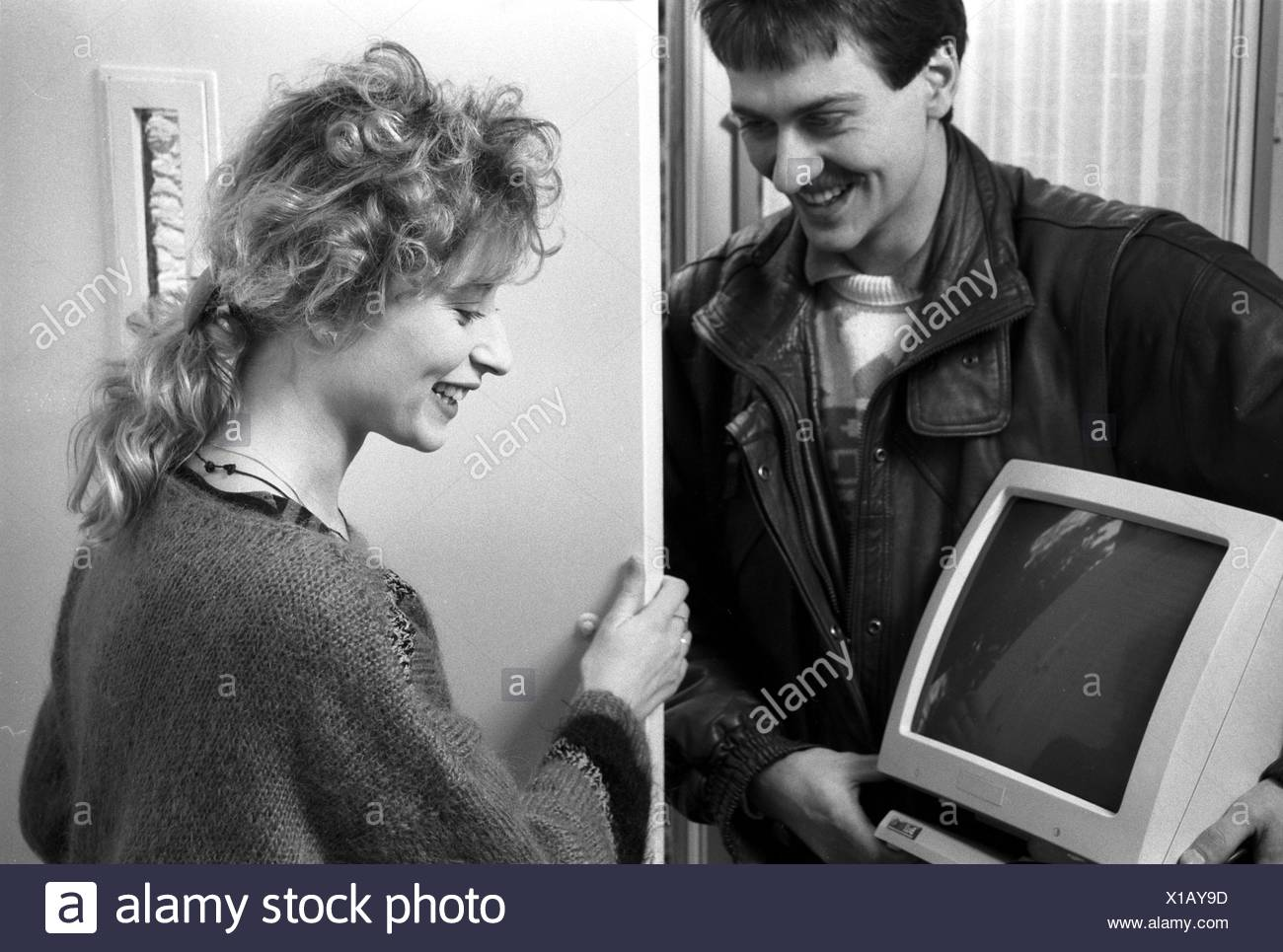 1981 Woman getting her first computer from man standing at front door holding computer screen in his hands, both smile - Stock Image
