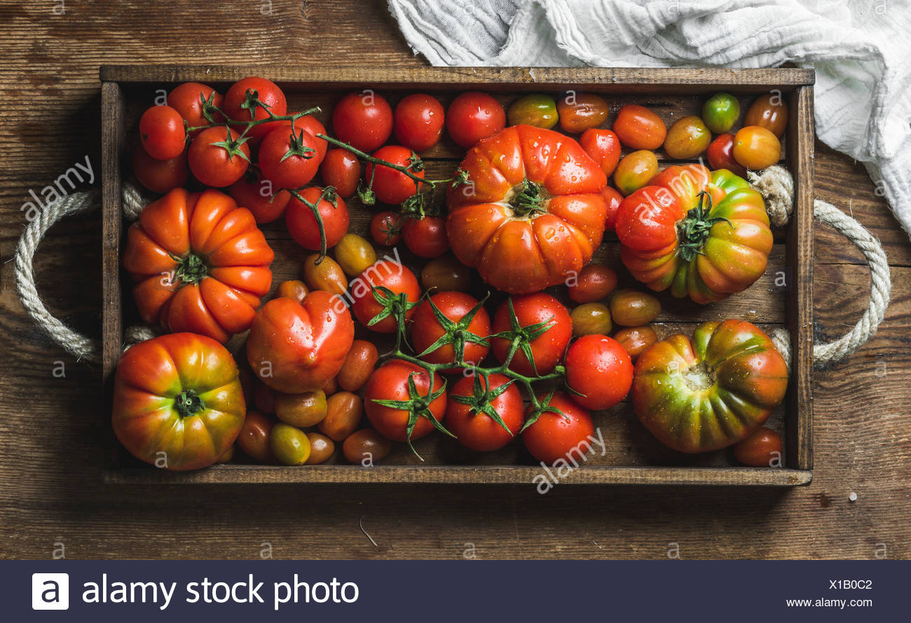 Colorful Heirloom tomatoes in rustic wooden tray over dark wooden background, top view, horizontal composition Stock Photo