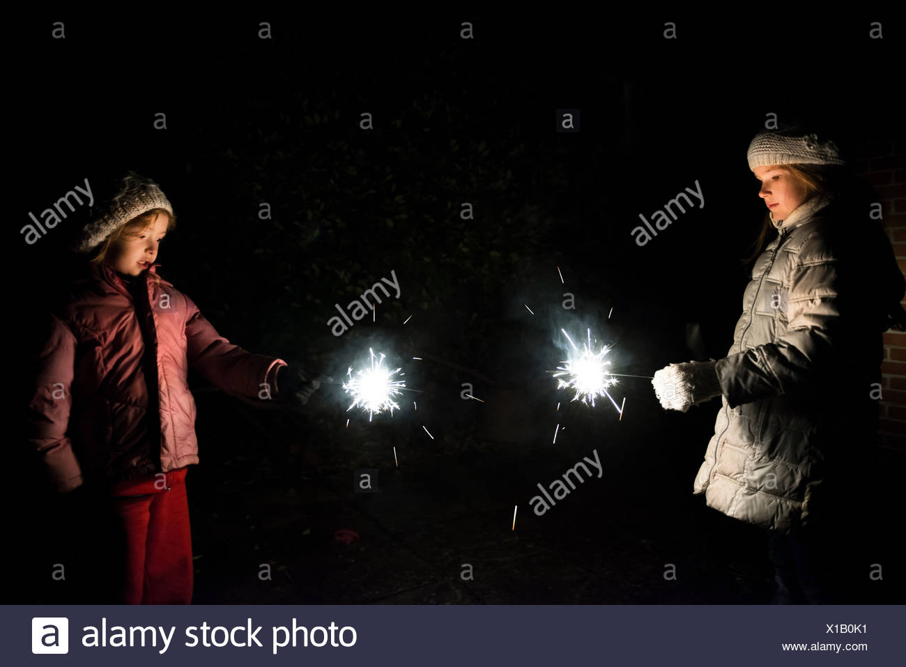 Sisters holding sparklers at night - Stock Image