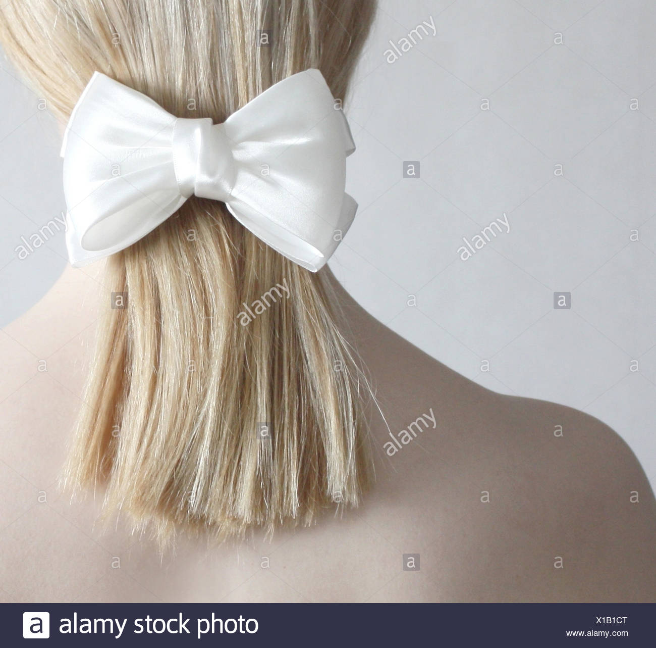 Rear view of blonde woman with a pony tail and white bow - Stock Image