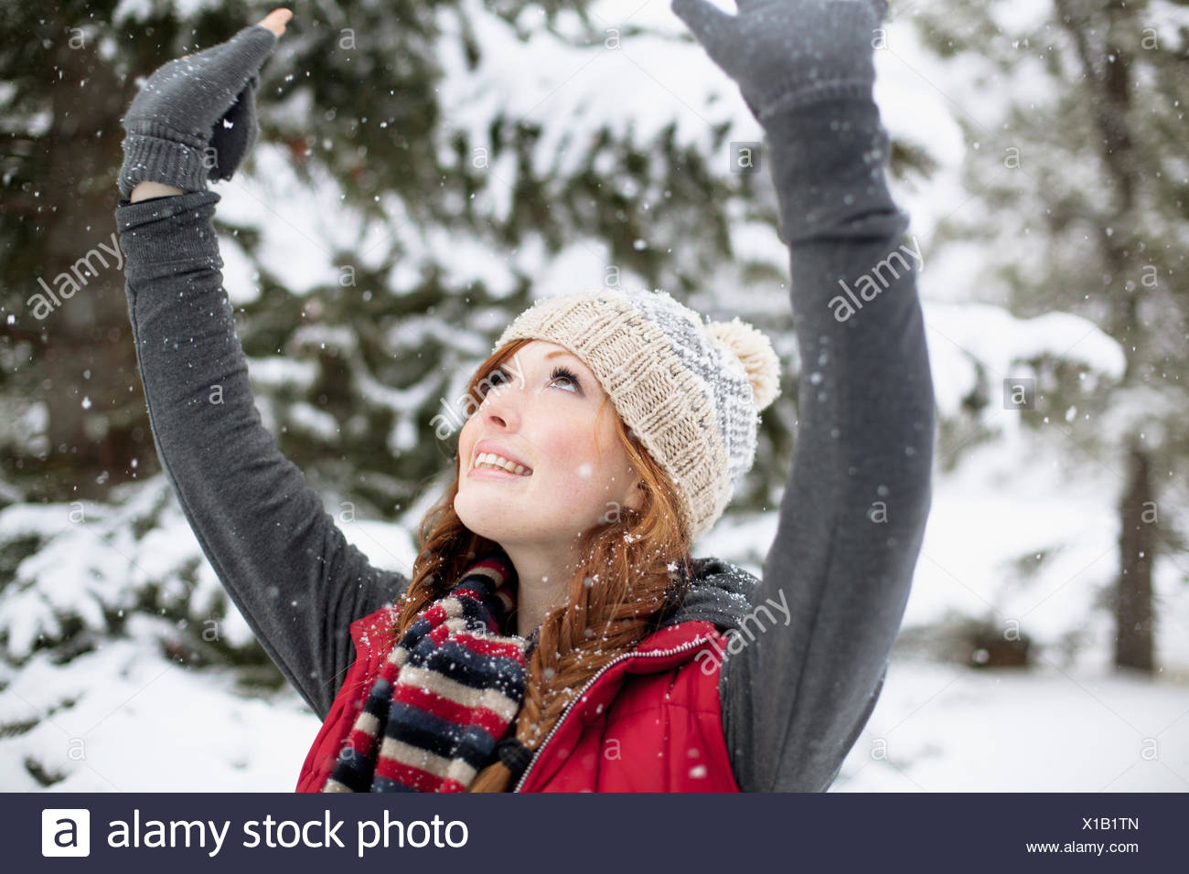 redheaded woman with arms outstretched - Stock Image