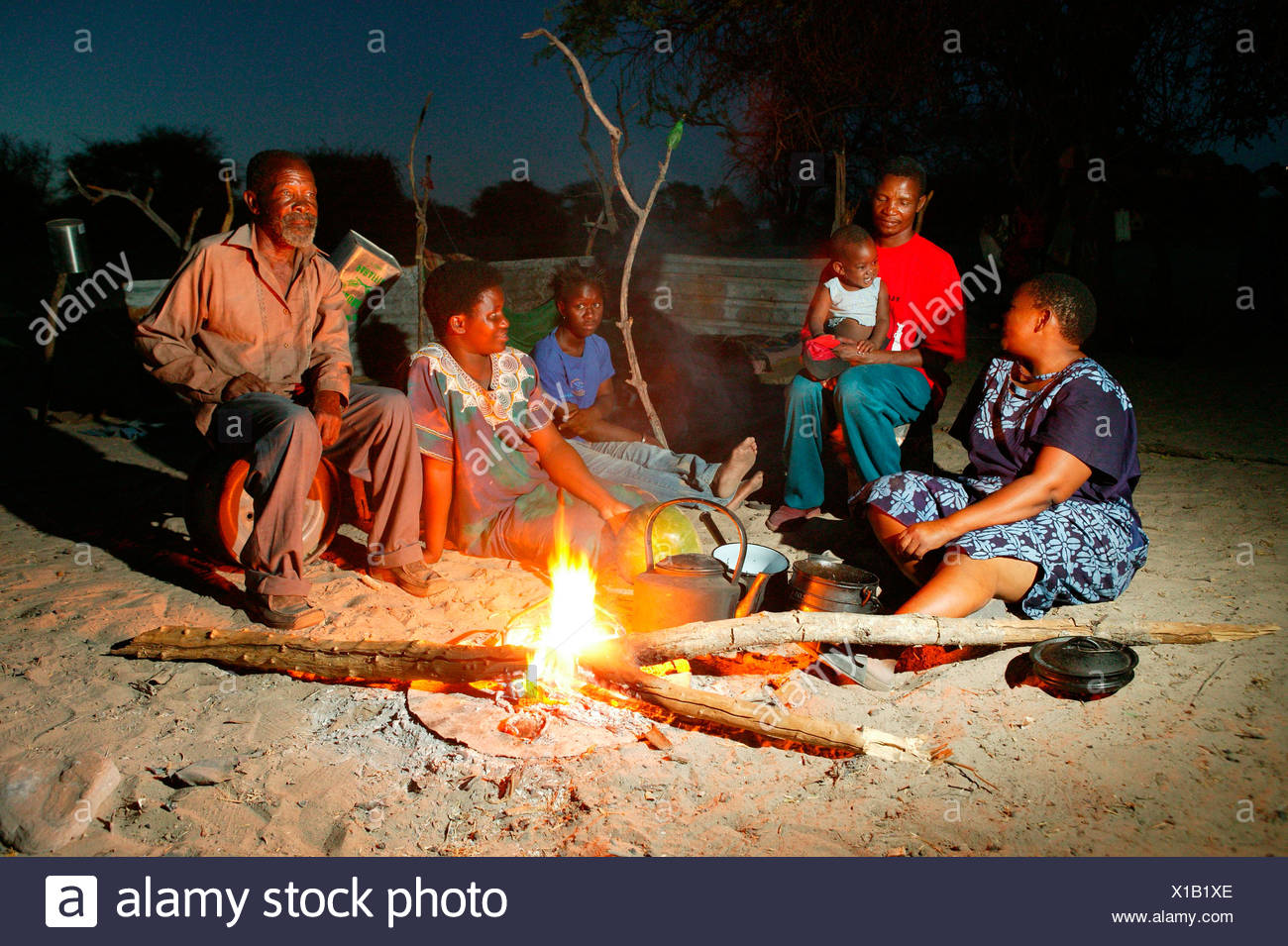 Group of people at the campfire, Cattlepost Bothatoga, Botswana, Africa - Stock Image