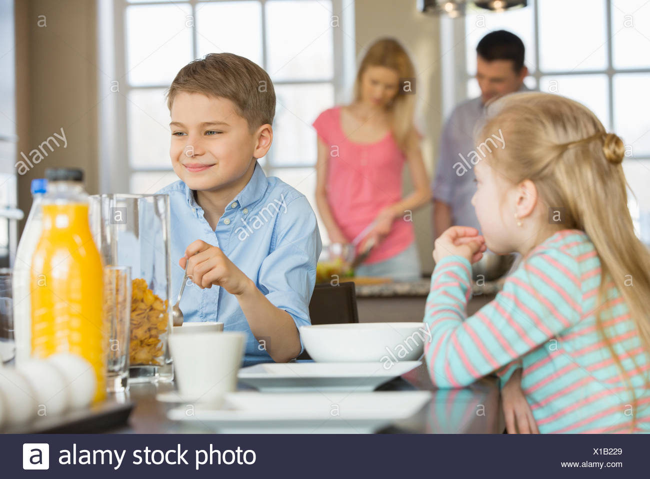 Siblings having breakfast at table with parents cooking in background - Stock Image