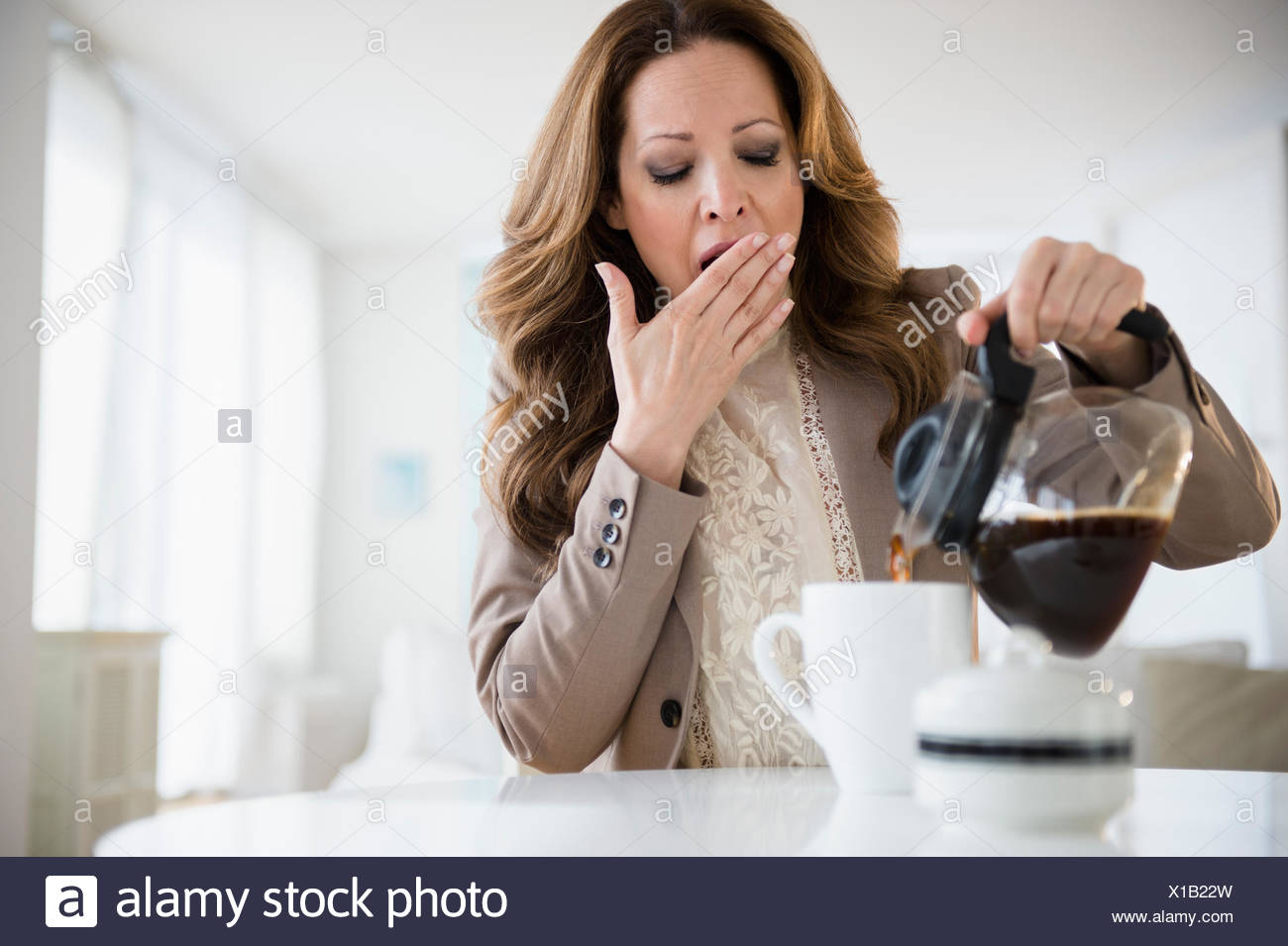 Yawnging woman pouring coffee - Stock Image