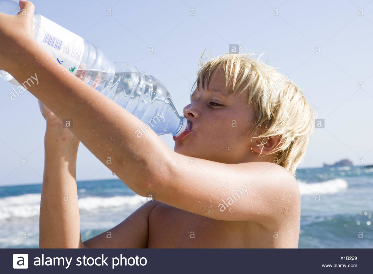 Beach, boy, thirsty, water Bottle, drink, portrait, side view, people, children, blond, summer holidays, holidays, sunny, heat, hotly, thirst, drink, Bottle, water, sea, thirst quencher, mineral water, - Stock Image