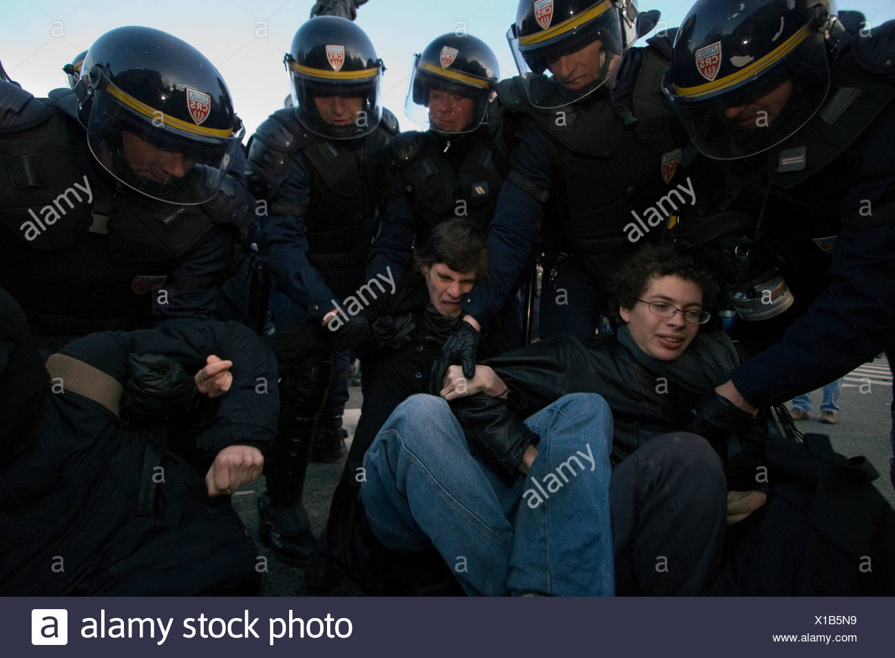 Riot policemen arrest protestors at the end of a rally. - Stock Image