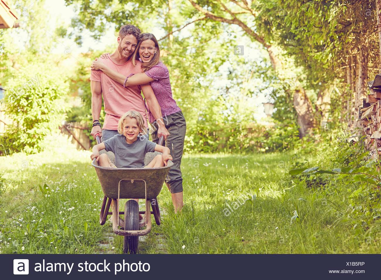 Portrait of young family, father pushing son in wheelbarrow - Stock Image