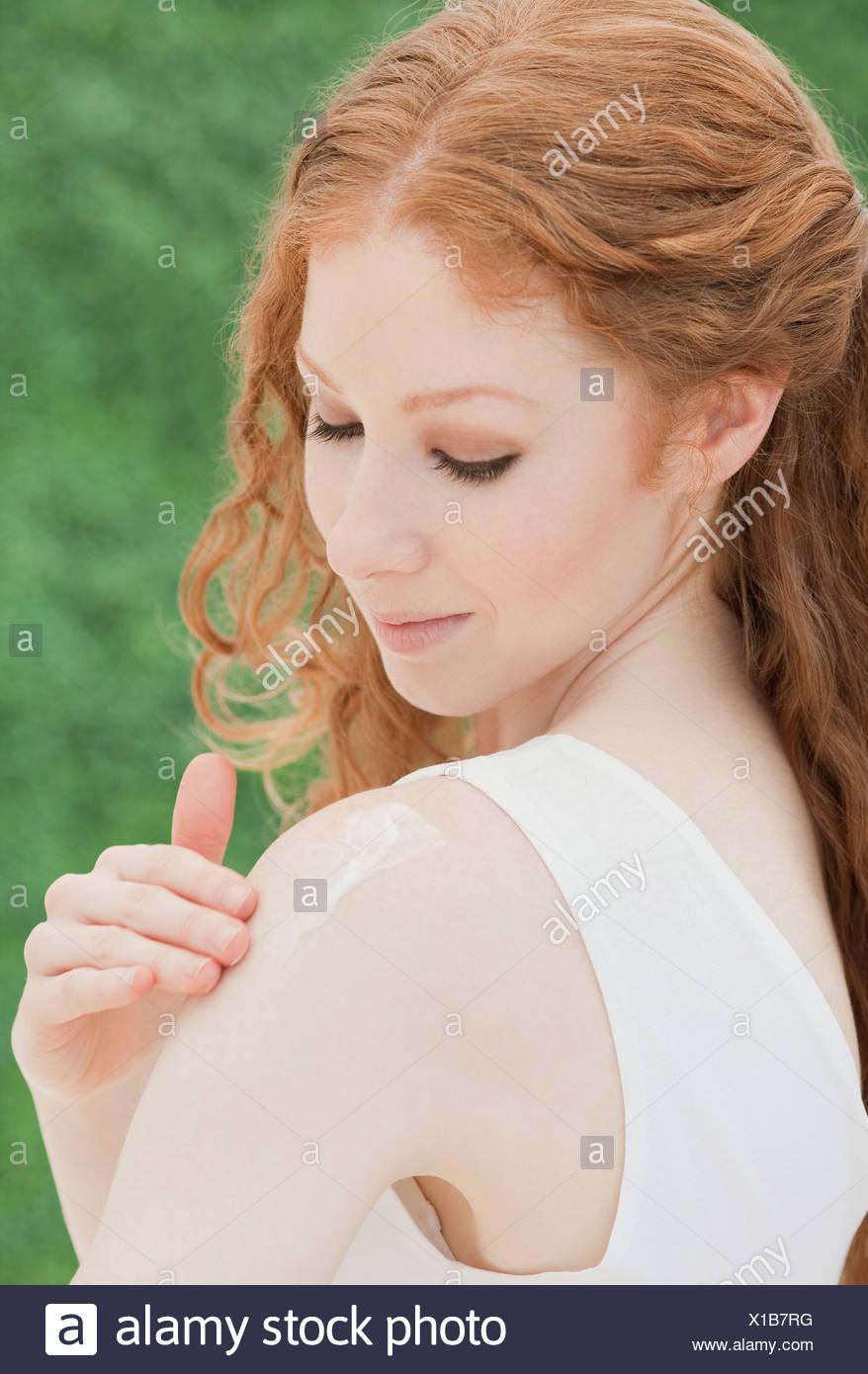 Woman applying lotion - Stock Image