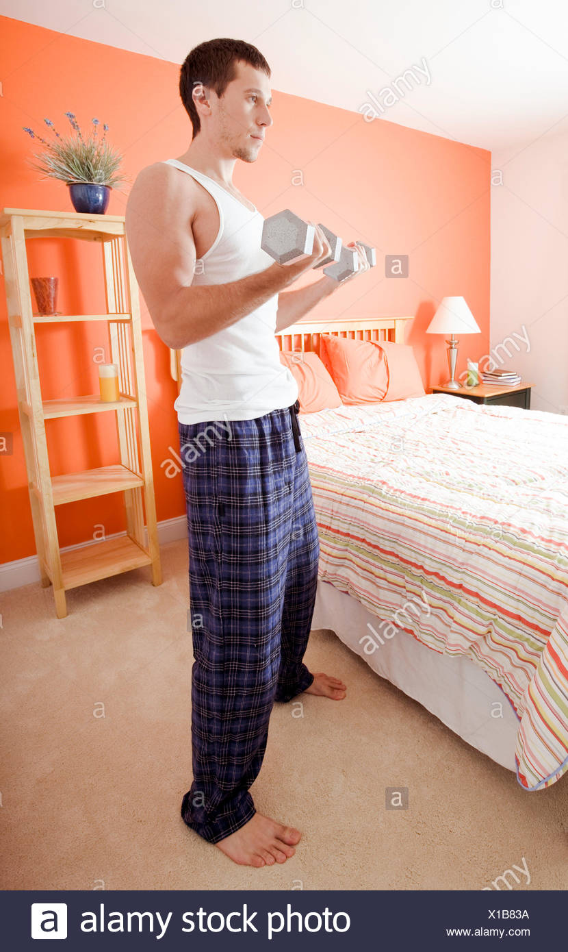 guy bedroom morning exercise weights exercising fitness man tomorrow home - Stock Image